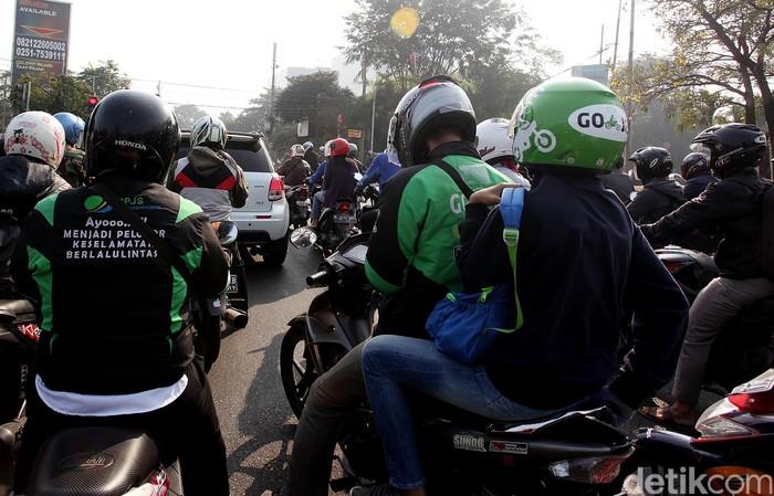 Pengemudi Go-Jek mengantar pelanggan. Foto: Rengga Sancaya
