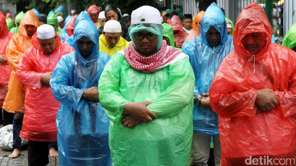 Momen Khusyuk Massa Salat Jumat Berjas Hujan