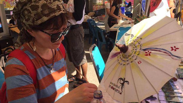 Wisatawan asyik melukis payung (Andi Anissa/detikTravel)