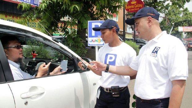 Direktur Komersial Jukir Arif Fadilah (kanan), menyaksikan seorang juru parkir melakukan transaksi melalui smartphone dengan seorang pengendara mobil.