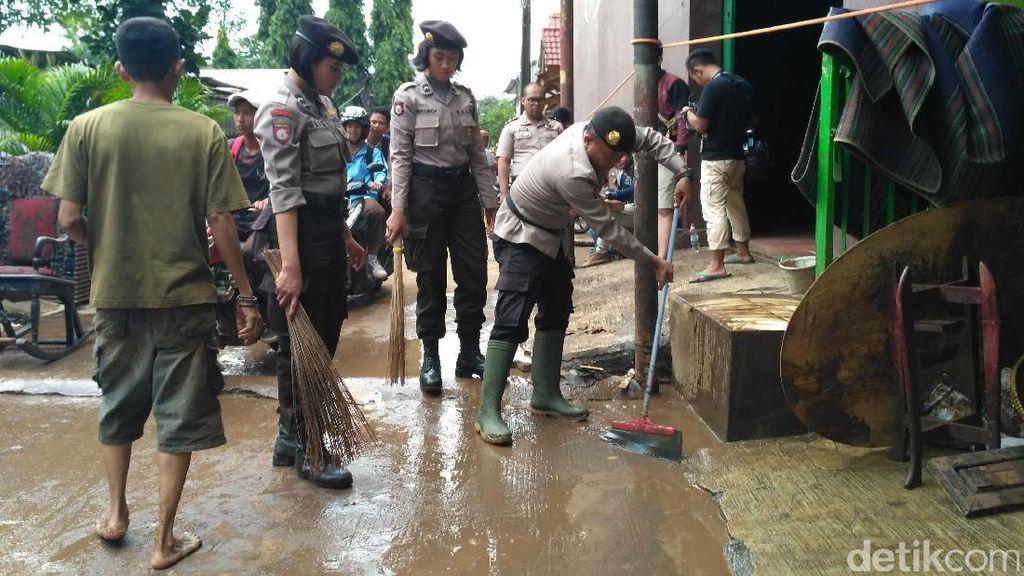 Polisi Bantu Warga Cipinang Melayu Bersihkan Sampah Sisa Banjir