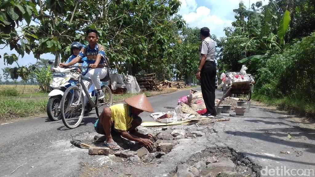 Aksi Kakek Pemulung Tambal Jalan Berlubang Pakai Uangnya Sendiri