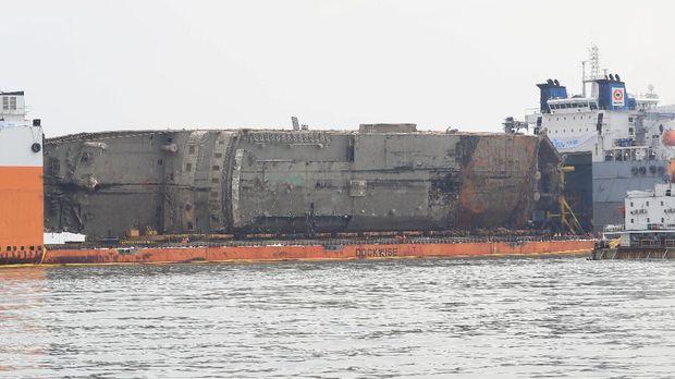 Bangkai kapal Sewol setelah diangkat dari dasar laut dan disiagakan di antara dua kapal semi-selam pada 26 Maret
