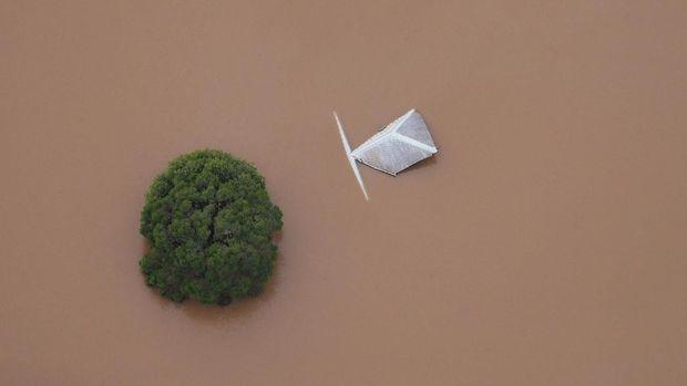 Hanya bagian atas pohon dan atap gedung yang terlihat di tengah banjir di kota Lismore, New South Wales