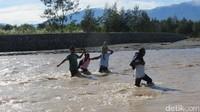 Warga Timor Leste menantang arus deras Sungai Malibaka di Turiskain, Kecamatan Raihat, Kab Belu. Mereka menyeberang ke Indonesia untuk pergi ke pasar (Fitraya/detikTravel)
