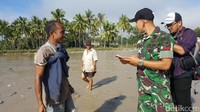 Anggota TNI dari Satgas Pamtas Batalyon Infantri Raider 641/Beruang memeriksa dokumen pelintas batas. Mereka sangat ramah kepada warga (Fitraya/detikTravel)