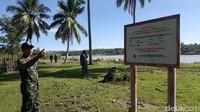 Aparat TNI menunjukan plan tanda perbatasan Indonesia dan Timor Leste. Di seberang Sungai Malibaka adalah negara Timor Leste (Fitraya/detikTravel)