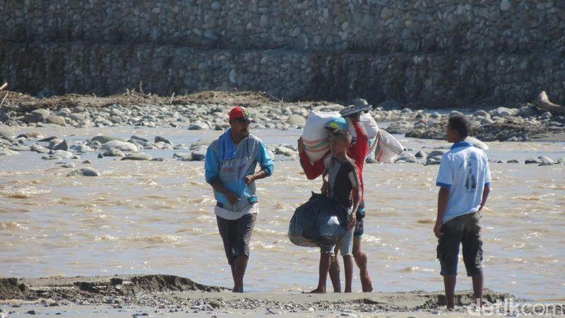 Warga Timor Leste menyeberangi Sungai Malibaka yang sangat lebar tanpa jembatan. Pernah ada yang tewas karena hanyut terbawa arus sungai yang deras (Fitraya/detikTravel)