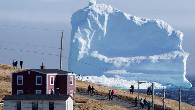Gunung es yang tampak begitu besar di permukaan laut belakang rumah penduduk. Traveler pun banyak yang penasaran untuk melihatnya langsung (Jody Martin/Reuters)