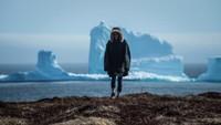 Seorang traveler berfoto di depan gunung es. Memang tak sedikit yang mengabadikan pesona gunung es ini di dalam kamera (Greg Locke/Reuters)