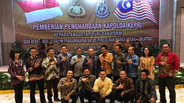 Kapolda Riau Irjen Pol Sam Budi Gusdian memberikan penghargaan kepada 38 polisi Malaysia atas kerjasama pengungkapan kasus penculikan Ling Ling.