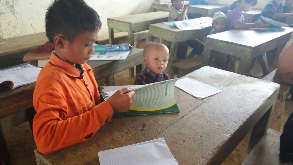Potret Haru Siswa Belajar di Sekolah Sambil Asuh Adiknya