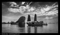 Kapal pesiar di Halong Bay yang agak gelap, kontras dengan langit di belakang yang terang dan dramatis membuat foto lebih menarik.