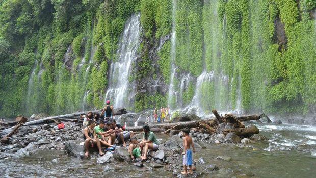 Wisatawan yang tengah menikmati segarnya air terjun (Air Terjun Asik-asik/Facebook)