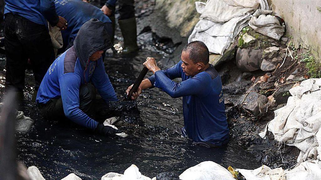 Pasukan Biru Nyemplung ke Got Hitam untuk Bersihkan Lumpur