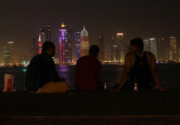 Beberapa warga duduk sambil meliat pemandangan indah pencakar langit di ibu kota Qatar, Doha. Situasi di sana tampak normal saja. Foto: Reuters