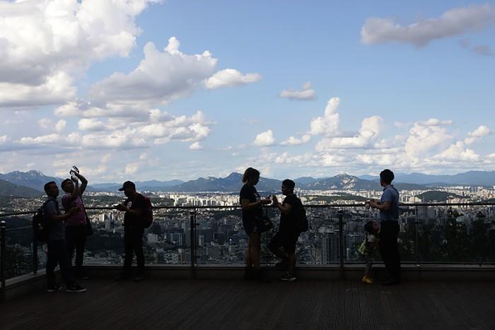 Meski Seoul sangat dekat dengan Korut dan terancam bahaya, warga masih tampak biasa saja. Ini mereka yang sedang menikmati keindahan kota dari N Seoul Tower. Foto: Getty Images