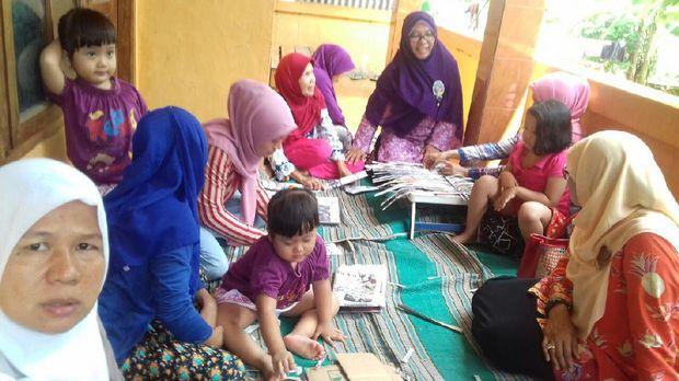Ibu-ibu membuat kerajinan dari koran bekas