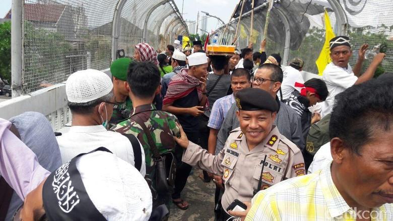 Polisi Bujuk Massa Aksi Turun - Jakarta Massa Aksi memenuhi jembatan penyeberangan orang di depan gedung Polisi datang mengimbau massa untuk ke bawah demi