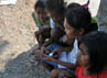 Bocah-bocah perempuan bermain game di seluler.
