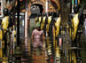 Seorang warga berjalan di depan sebuah kuil di distrik Don Muang, Bangkok yang terendam banjir. Reuters/Sukree Sukplang.