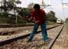 Para pekerja menggeruk batu yang menutupi rel kereta api yang digunakan sebagai perlintasan sepeda motor.