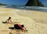 Anak-anak asyik bermain pasir di Pulau Merah.