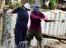 Beberapa pekerja memasang turap yang terbuat dari beton.
