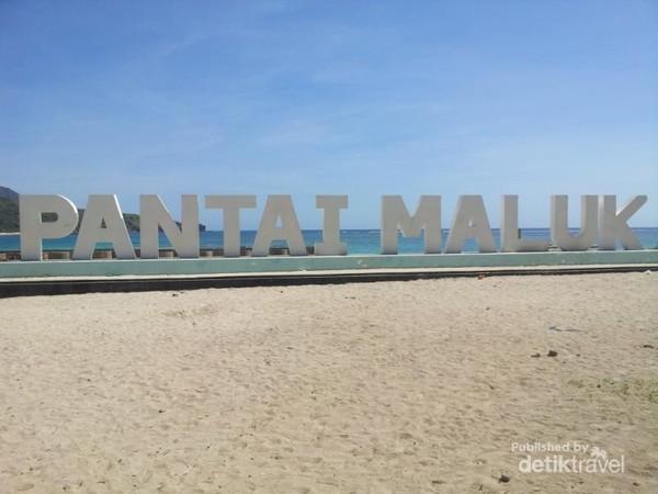 Di depan pantai, terdapat ikon tulisan nama Pantai Maluk