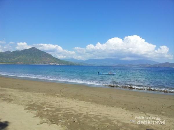Suasana pemandangan pantai Poto Balat dimana pantainya di kelilingi pegunungan yang hijau dan pasir cokelat terhampar seperti permadani