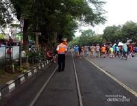 Petugas keamanan menghalau warga saat kereta melintas