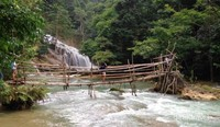 Menyebrangi sungai melewati jembatan bambu