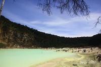 Hamparan air kawah yang berwarna hijau dan indahnya langit biru yang dibatasi bentangan tebing yang menjulang