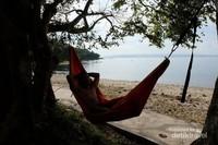 Bersantai di pinggir pantai, sambil menikmati keindahannya.