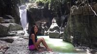 Duduk santai sambil menikmati pemandangan air terjun memberikan kedamaian tersendiri