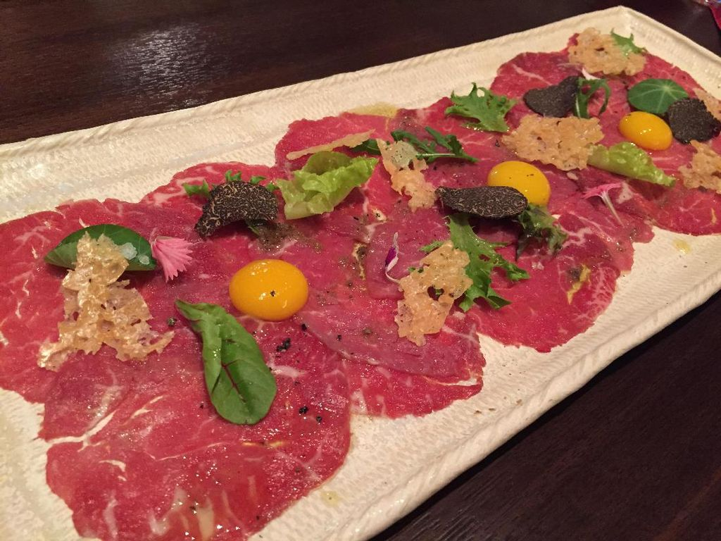 Suguhan menu pembuka lainnya berupa Carpaccio di Wagyu. Lembaran tipis wagyu mentah diberi topping kunng telur puyuh, black truffle, herba dan parmesan chips.