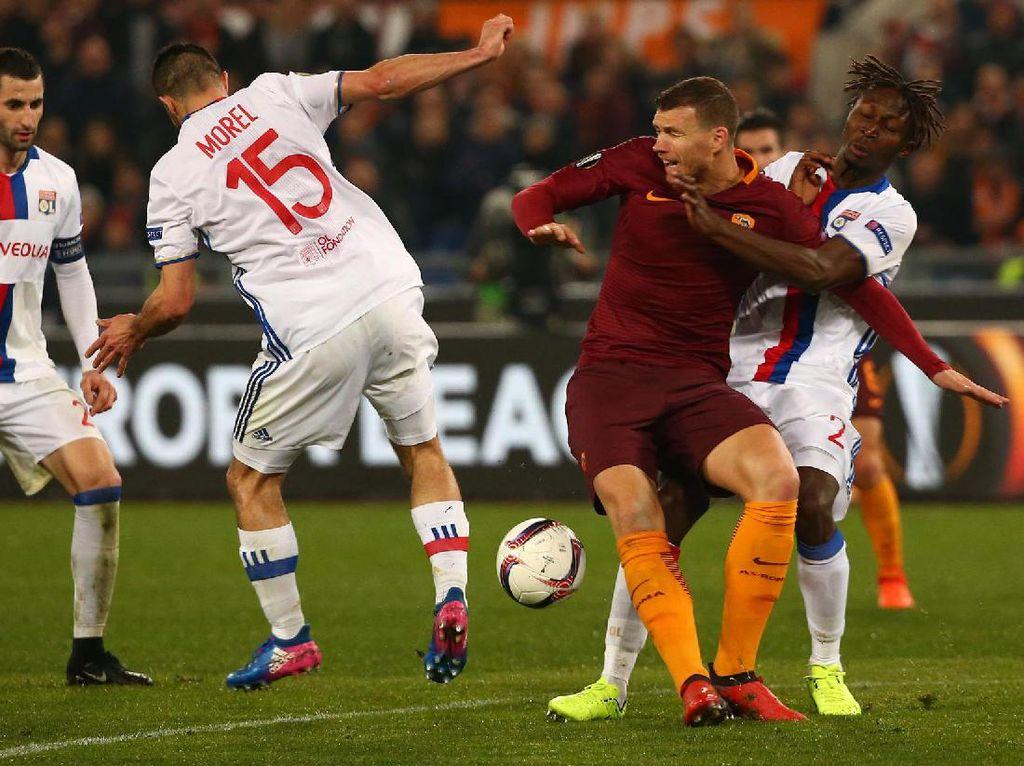 Tiga pemain Olympique Lyon mengepung Edin Dzeko untuk menghentikan serangan pesepakbola asal Bosnia-Herzegovina tersebut.