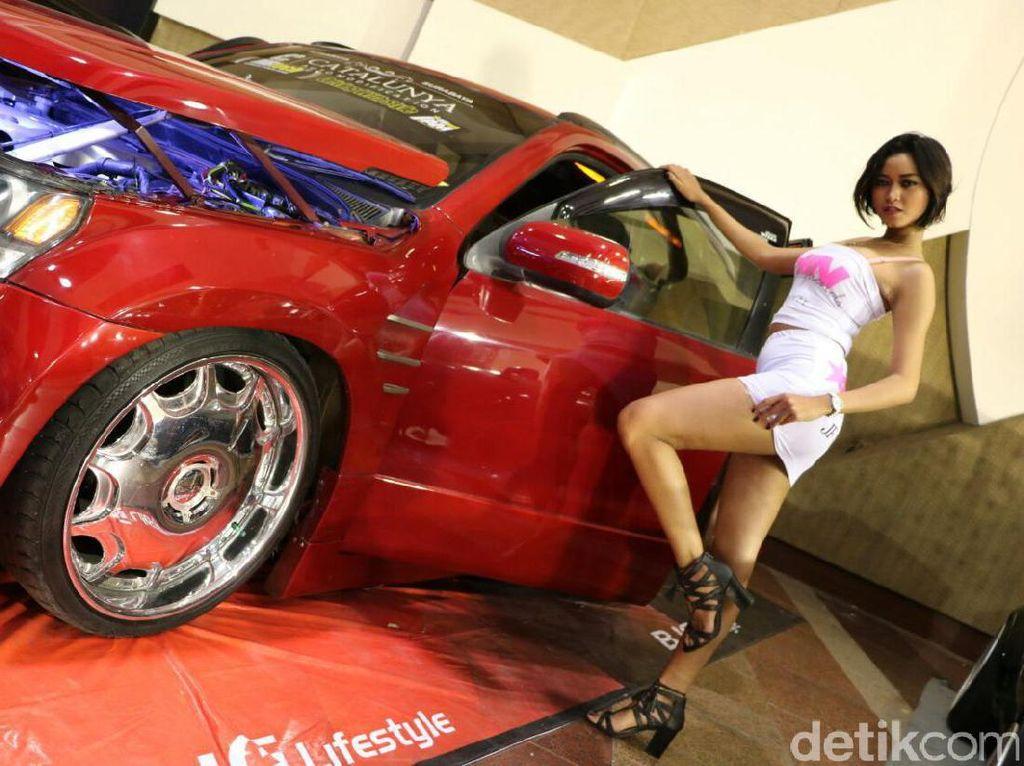 Seorang model Hot Import Nights berpose dengan sebuah mobil modifikasi berwarna merah di Indonesia Automodified (IAM) MBtech 2017 di Surabaya. Foto: Rangga Rahadiansyah