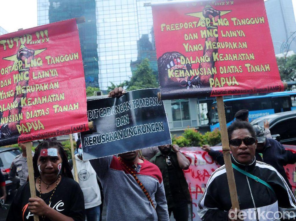 Demonstran membentangkan poster-poster tuntutan di depan kantor PT Freeport Indonesia.