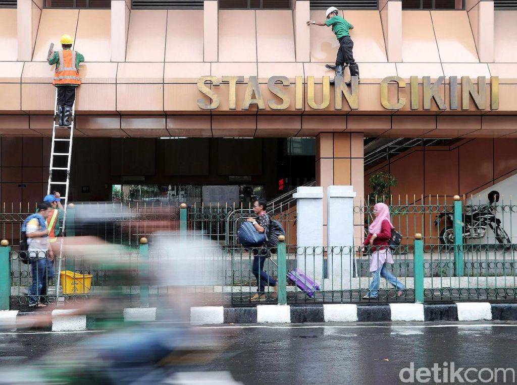 Pekerja membersihkan dinding Stasiun Cikini, Jakarta Pusat.
