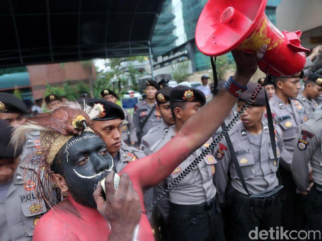 Perwakilan aksi berorasi di depan barikade polisi.