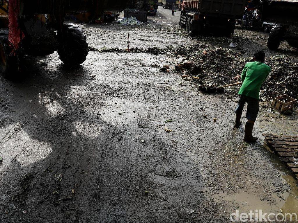 Seorang pekerja membersihkan tumpukan sampah sisa akitifitas jual beli.