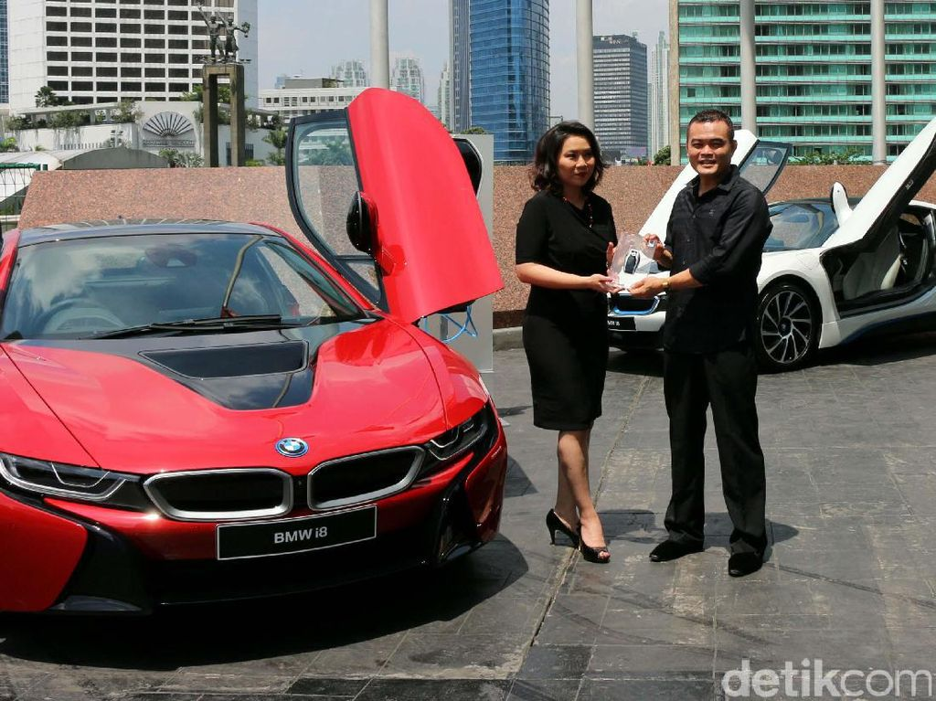 President Director of BMW Group Indonesia Karen Lim menyerahkan kendaraan kepada pemilik pertama unit mobil hybrid BMW i8 Protonic Red Edition, Sonny Kastara di Jakarta, Kamis (20/4/2017).