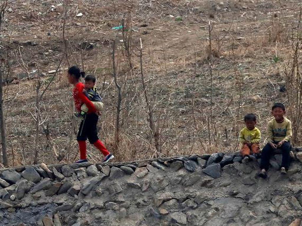 Para penduduk Korut di daerah yang terlihat gersang. Foto: Reuters