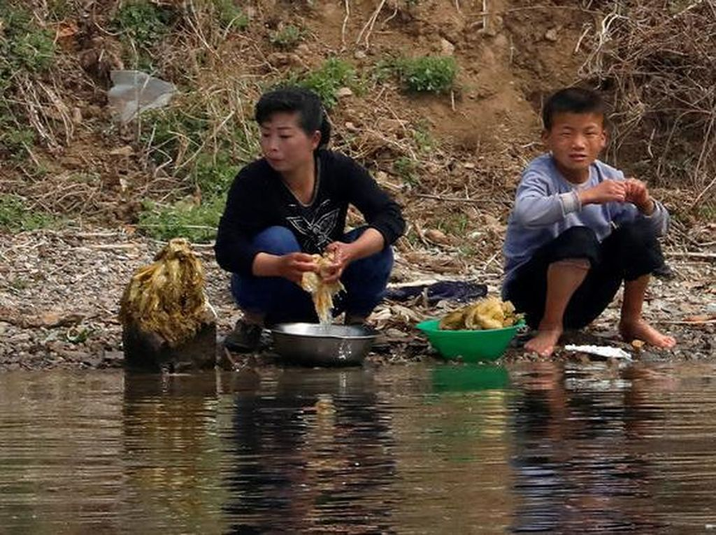 Tampak penduduk daerah perbatasan Korut sedang mencuci sayuran di sungai Yalu. Foto: Reuters