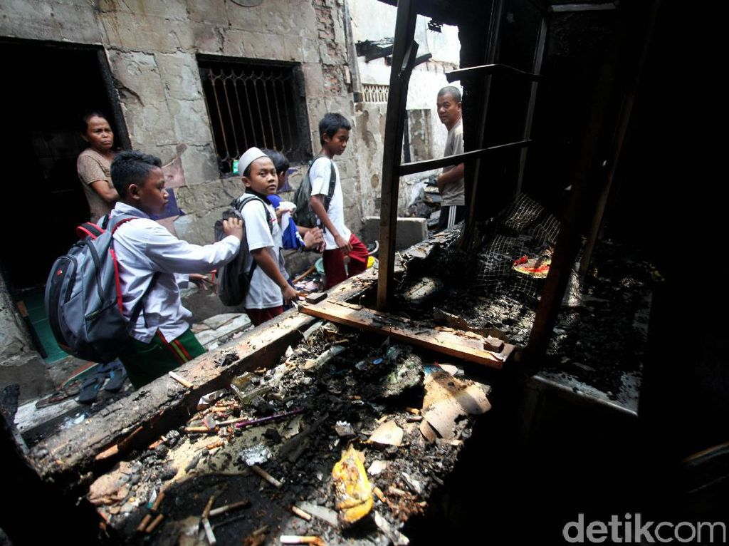 Sejumlah siswa SD tengah berjalan diantara puing-puing rumah yang terbakar.