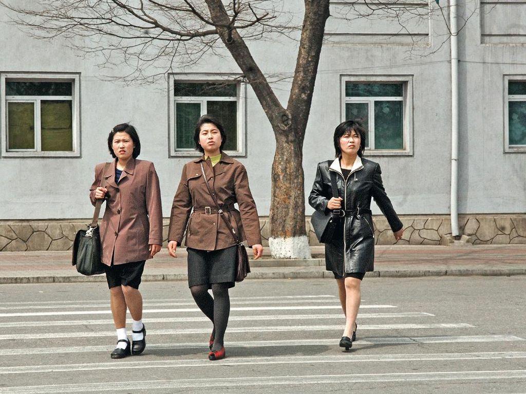 Tiga wanita melintas di jalanan Pyongyang yang sepi, dengan busana seragam. Foto: Hufpost