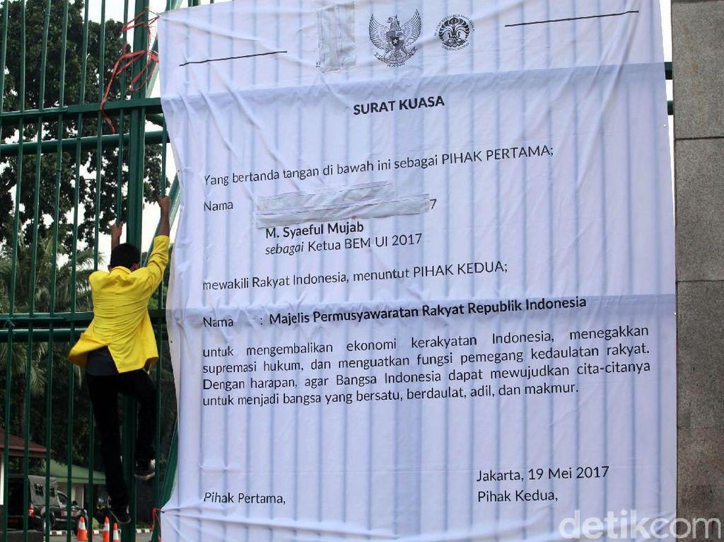 Demonstran juga memasang spanduk tuntutan di pagar gedung DPR.