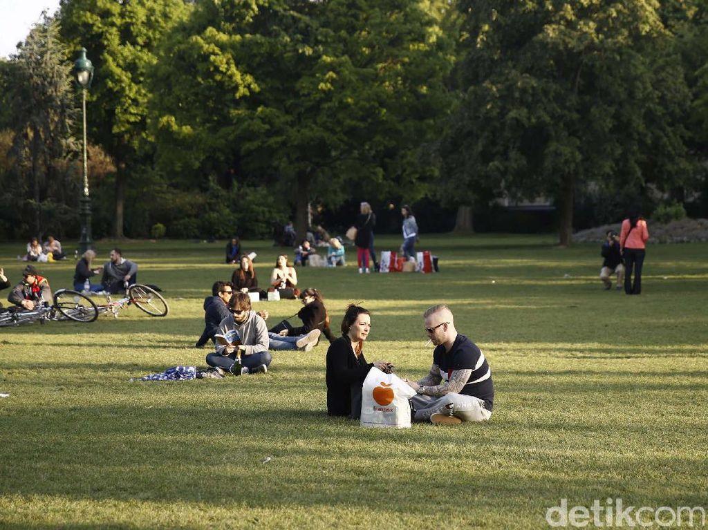 Wisatawan bersantai di taman kawasan Menara Eiffel.