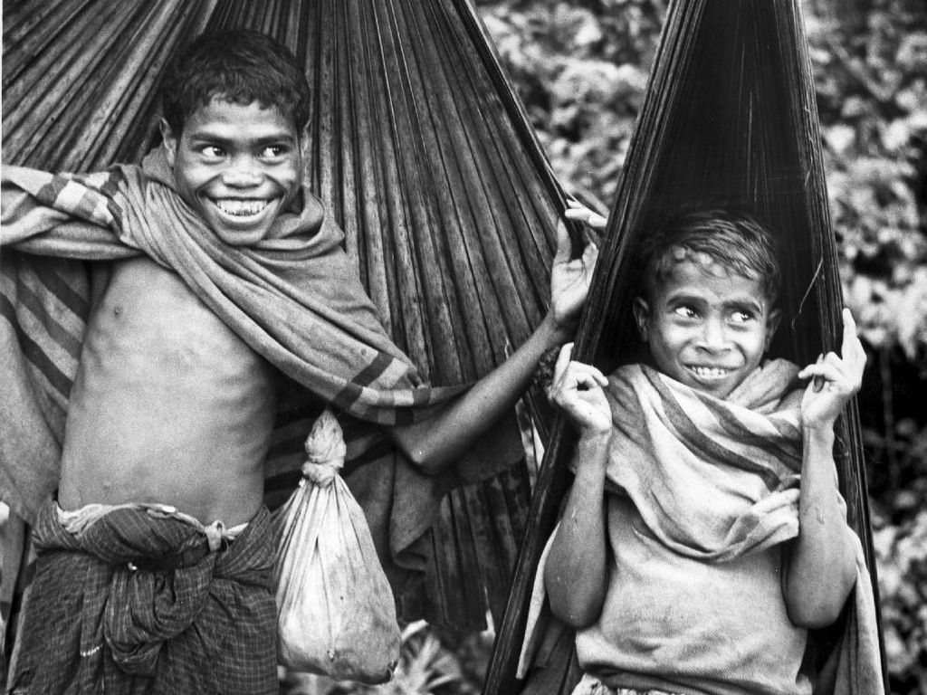 Dua bocah tengah berteduh menggunakan daun lontar di wilayah Indonesia bagian timur tahun 1950. Richard Harrington/Getty Images.